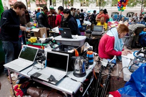 Los manifestantes del grupo Occupy Wall Street que han acampado durante más de dos semanas en el Distrito Financiero de Nueva York tienen un área de medios donde actualizan las noticias en computadoras portátiles alimentadas por energía de generadores a base de gas el domingo 2 de octubre de 2011. (Foto AP/John Minchillo)