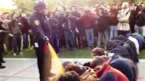 Un policía rocía pimienta con un atomizador a una hilera de manifestantes sentados en la Universidad de California en Davis, el viernes 18 de noviembre de 2011. (AP foto/Thomas K. Fowler)