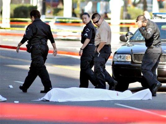Policías de Los Angeles pasan junto a un cadáver tras el ataque con arma de fuego de un hombre de 26 años, sin un objetivo aparente, contra conductores el viernes 9 de diciembre de 2011 en Los Angeles. El ejecutivo musical John Atterberry murió el lunes 12 de diciembre de 2011 tras sufrir el ataque del hombre, informaron autoridades del hospital en el que se encontraba Atterberry. (Foto AP/ Josh Edelson)