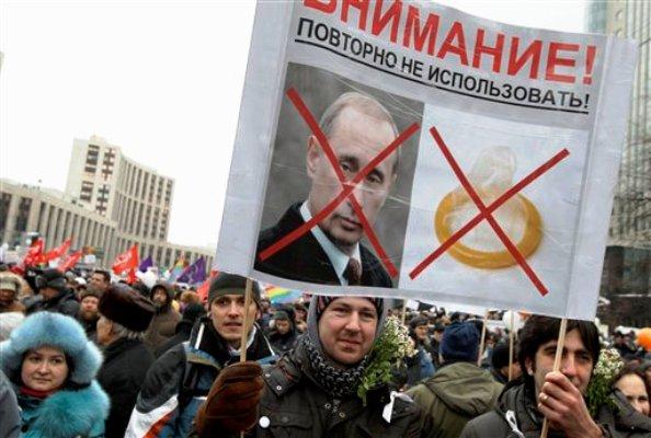 """Unos manifestantes sostienen un cartel con la fotografía del primer ministro ruso Vladimir Putin junto a la imagen de un condón, bajo una inscripción que dice """"Utilizar sólo una vez"""", mientras protestan contra una presunta manipulación de votos en las elecciones parlamentarias rusas, en la avenida Sakharov en Moscú, el sábado 24 de diciembre de 2011. (Foto AP/Ivan Sekretarev)"""
