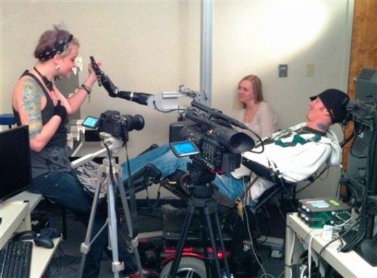 El parapléjico Tim Hemmes ensaya un brazo electrónico que opera mediante un chip instalado en su cerebro. Lo asiste Katie Schaffer (izq) en el Centro Médico de la Universidad de Pittsburgh. Foto del 19 de septiembre del 2011, suministrada por la universidad. (AP Photo/UPMC, file)