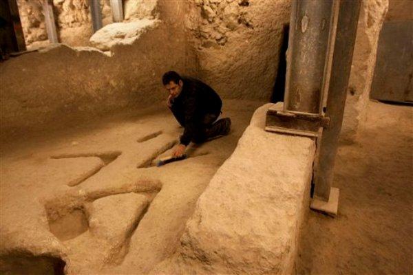 En esta foto del 1 de diciembre del 2011, el arqueólogo Eli Shukron, de la Autoridad de Antigüedades de Israel, examina tallas en piedra que datan de hace miles de años y que fueron descubiertas en una excavación en Jerusalén (AP Foto/Sebastian Scheiner)