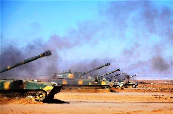 """Tanques del ejército sirio abren fuego durante maniobras efectuadas en una ubicación no precisada en Siria, de acuerdo con esta fotografía que facilitó el domingo 4 de diciembre la agencia noticiosa oficial del país. La prensa estatal dijo que las maniobras se efectuaron el domingo e incluyeron disparo de misiles y operaciones coordinadas entre la fuerza aérea y efectivos en tierra """"similares a una batalla de verdad"""". (AP foto/SANA)"""