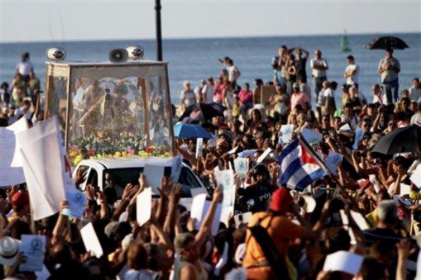 Fieles católicos asisten a una misa al aire libre en honor de la Virgen de la Caridad del Cobre en La Havana, Cuba, el viernes 30 de diciembre de 2011. Unas 3.000 personas se congregaron el viernes por la tarde en la Avenida del Puerto, último punto por donde pasó la Virgen patrona tras 16 meses de andar a lo largo de 30.000 kilómetros, la primera peregrinación nacional en más de cinco décadas. (AP foto/Franklin Reyes)