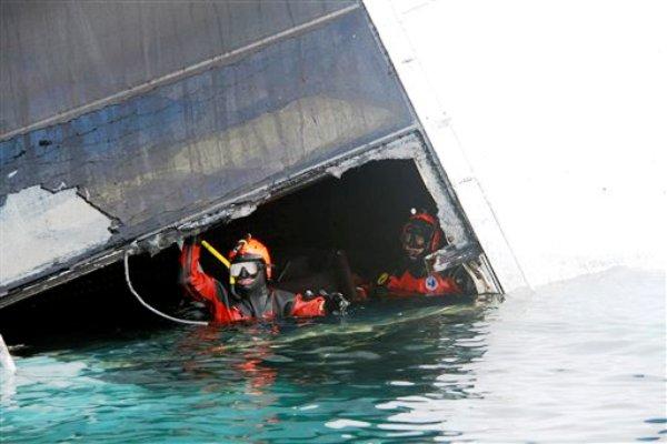En esta fotografía sin fechar  hecha por los bomberos italianos y difundida el lunes 23 de enero de 2012 se ven buzos que inspeccionan el barco encallado en las aguas toscanas, junto a la isla de Giglio en Italia. (Foto AP/Vigili del Fuoco)