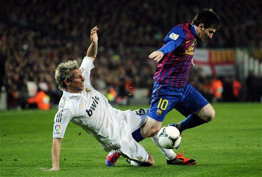 Foto de archivo. Coentrao y Messi disputan una pelota en un partido entre el Barcelona y Real Madrid. Foto AP.