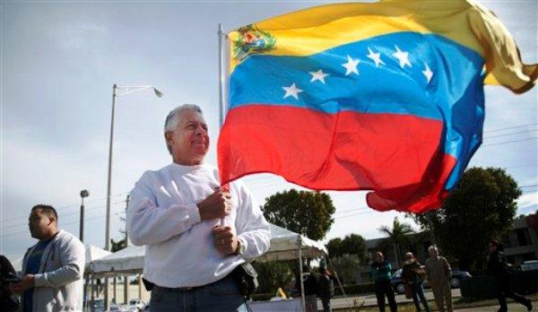 Martín Sanabria sostiene una bandera de Venezuela frente a una casilla electoral, en Doral, Florida, el domingo 12 de febrero de 2012, donde miles de venezolanos llegaron para elegir a un candidato de oposición que enfrentará al presidente Hugo Chávez en los comicios presidenciales de octubre en Venezuela. (Foto AP/J Pat Carter)