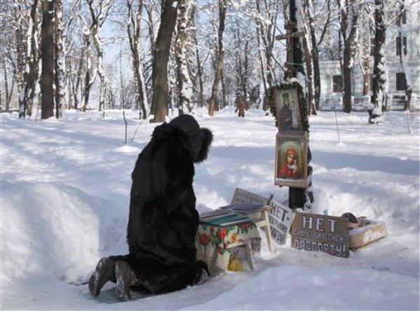 Una mujer reza entre árboles cubiertos de nieve en un parque en la ciudad de Kiev, Ucrania, el martes 31 de enero de 2012. Las autoridades ucranianas afirmaron el miércoles que al menos 43 personas han muerto de frío en el país. (AP foto/Efrem Lukatsky)