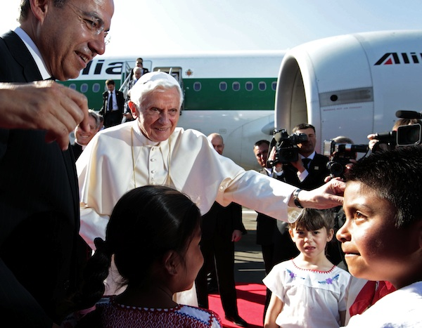 El presidente Felipe Calderón, a la izquierda, observa mientras el Papa Benedicto XVI es recibido por unos niños en el aeropuerto de Silao, México, el viernes 23 de marzo de 2012. Es la primera ocasión en que el actual Papa visita México. (AP foto/Gregorio Borgia)