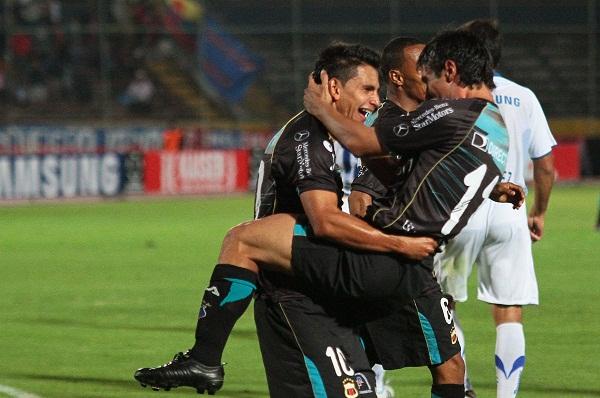 Luis F. Saritama (izq.) y Matías Alustiza (der.), ambos anotadores de goles, celebran la tercera conquista.