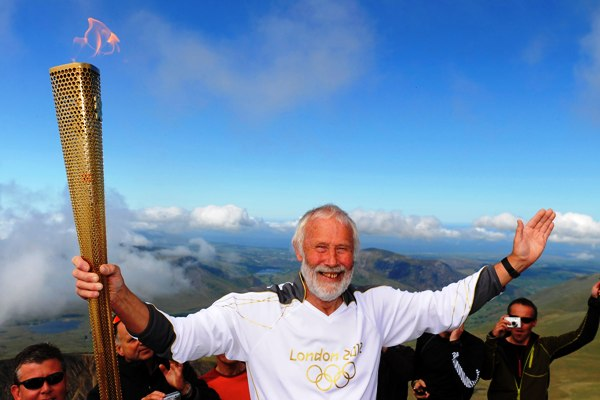British mountaineer Chris Bonnington holds the Olympic flame on top of Snowdon, the highest peak in Wales, in Snowdonia National Park, Wales May 29, 2012.  The flame was carried through Wales on day 11 of the Torch Relay, as part of the London 2012 Olympic Games.  REUTERS/LOCOG/Handout    (BRITAIN - Tags: SPORT OLYMPICS SOCIETY) NO SALES. NO ARCHIVES. FOR EDITORIAL USE ONLY. NOT FOR SALE FOR MARKETING OR ADVERTISING CAMPAIGNS. THIS IMAGE HAS BEEN SUPPLIED BY A THIRD PARTY. IT IS DISTRIBUTED, EXACTLY AS RECEIVED BY REUTERS, AS A SERVICE TO CLIENTS