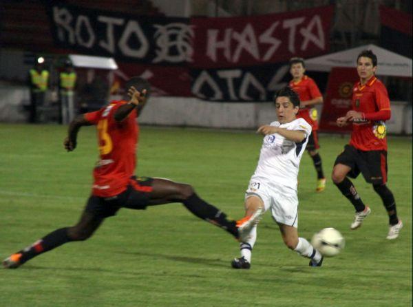 Henrry Cangá intenta arrebatarle la pelota Damián Manso de Liga de Quito.