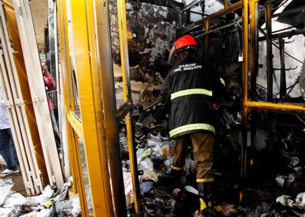 """Un bombero keniano observa los escombros en una tienda tras una explosión que se registró en un edificio lleno de pequeños locales comerciales en el centro de Nairobi, la capital de Kenia, el lunes 28 de mayo de 2012. El primer ministro del país indicó que el incidente fue deliberado y una mujer acusó a un """"hombre con barba"""" de haber dejado una bolsa en el lugar poco antes de la explosión. (Foto AP/Sayyid Azim)"""