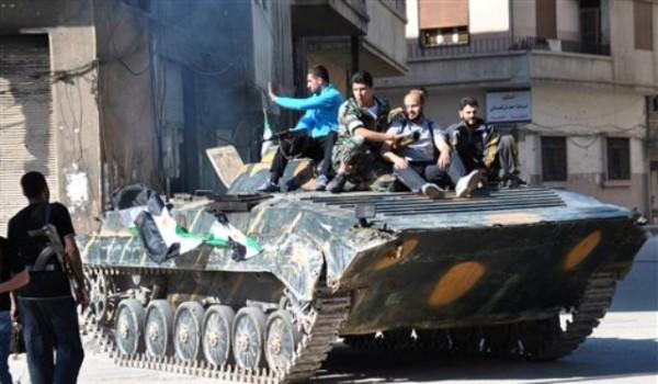 Soldados y rebeldes descansan juntos sobre un tanque de guerra blindado poco después de que los soldados del ejército sirio desertaron de las fuerzas del gobierno, en el distrito de Khaldiyeh, en la provincoa de Homs del centro de Siria, el sábado 12 de mayo de 2012. Las fuerzas sirias mataron al menos a cinco personas el domingo 13 de mayo en una redada en una villa agrícola del noroeste de Siria. (Foto AP/Fadi Zaidan)