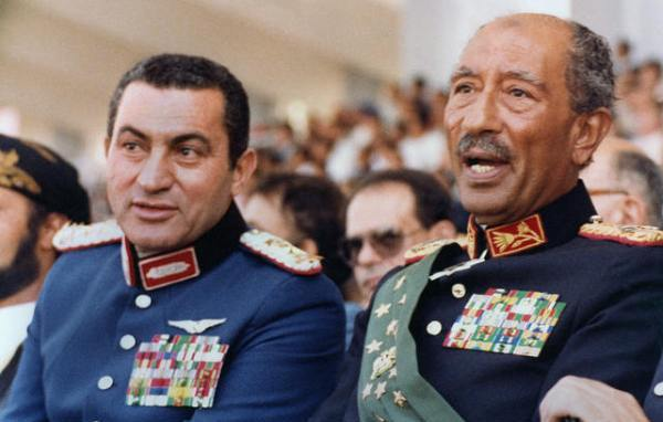 Egyptian vice President, Gen. Hosni Mubarak (L) and late President Anwar Sadat (R), both dressed in military honour uniforms, attend a military parade, 06 October 1981, in Cairo, commemorating Victory Day. Moments after, a group of military Islamist fundamentalists with allegiance to the Al-Jihad group killed Sadat in a shooting spree. Following Sadat's assassination Mubarak was sworn in as Egypt?s fourth president, a position of power he has since retained, being re-elected five times. AFP PHOTO/- (Photo credit should read AFP PHOTO/AFP/Getty Images)