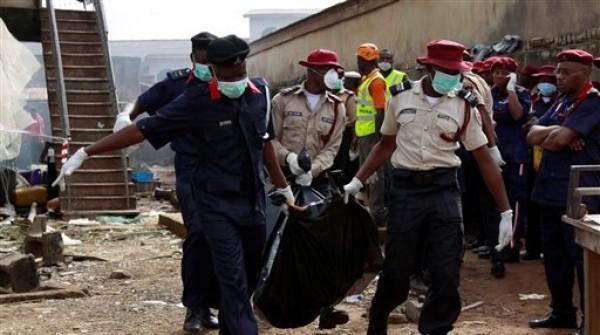 Trabajadores de rescate cargan cuerpos en el sitio del accidente aéreo en Lagos, Nigeria, el lunes 4 de junio de 2012. Un avión de pasajeros con más de 150 personas a bordo se estrelló en una zona residencial en lagos el domingo. (Foto AP/Sunday Alamba)