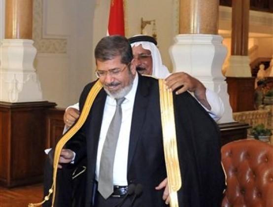 En esta fotografía proporcionada por la Presidencia de Egipto, el mandatario electo Mohammed Morsi  recibe la toga tradicional durante una reunión con representantes de partidos políticos, el jueves 28 de junio de 2012, en El Cairo, Egipto. (Foto AP/Egyptian Presidency)