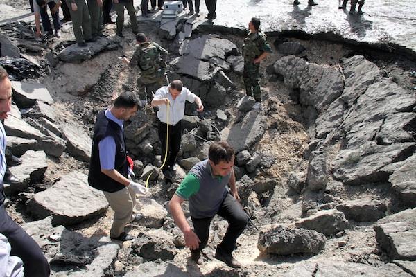 Las autoridades sirias investigan el cráter dejado por explosiones de dos coches bomba frente a un edificio militar de inteligencia del barrio de Qazaz en Damasco, Siria, el jueves 10 de mayo de 2012. Mientras las autoridades aseguran que el ataque fue perpetrado por insurgentes al frente del levantamiento contra el presidente Bashar Assad, un líder de la oposición en Siria aseguró el viernes 11 de mayo de 2012 que los agresores tienen vínculos con las fuerzas del país. (Foto AP/Bassem Tellawi)