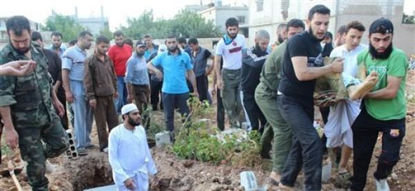 Esta imagen suministrada por Baba Amro In The Revolution's Eye en la localidad siria de Baba Amro muestra a opositores que entierran a un combatiente rebelde de ese lugar que murió durante un enfrentamiento con los soldados sirios. El sepelio, según la imagen, ocurrió el viernes 22 de junio de 2012. El presidente de Siria, Bashar Assad, anunció el sábado 23 un nuevo gobierno, que será encabezado por allegados al régimen. (Foto AP/Baba Amro In The Revolution's Eye) THE ASSOCIATED PRESS IS UNABLE TO INDEPENDENTLY VERIFY THE AUTHENTICITY, CONTENT, LOCATION OR DATE OF THIS HANDOUT PHOTO