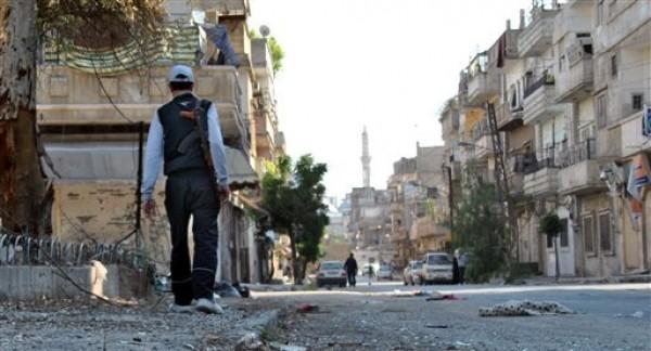 En imagen del martes 15 de mayo de 2012, un rebelde sirio camina en el vecindario Khaldiyeh de la provincia de Homs, en el centro de Siria. Naciones Unidas informó el miércoles 16 de mayo que espera evacuar en las próximas horas a un grupo de observadores internacionales que el martes se vio en medio de una zona bajo fuego en el norte del país y que al parecer quedó varado en el área durante toda la noche. (Foto AP/Fadi Zaidan)