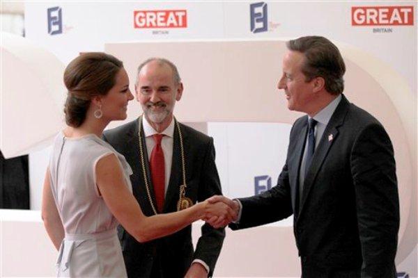 La duquesa de Cambridge saluda al primer ministro británico David Cameron, derecha, y el presidente de la Academia Real de Artes, Christopher Le Brun, al llegar a una recepción de la industria del entretenimiento ofrecida por el gobierno británico y Founders Forum en Londres el lunes 30 de julio de 2012. (Foto AP/ Sang Tan)