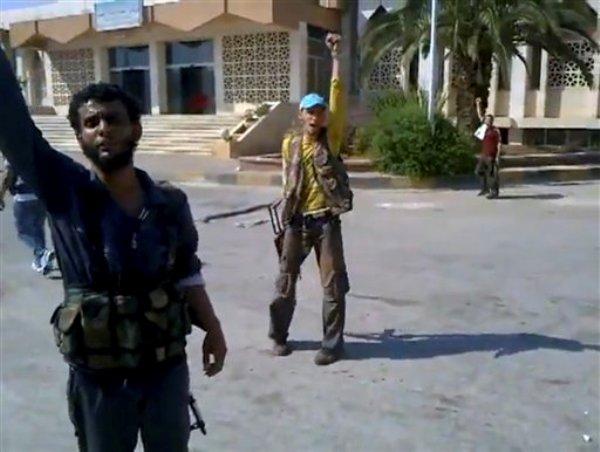 Rebeldes reaccionan mientras un compañero desfigura un cartel con el retrato del presidente Bashar Assad en una imagen captada en un video aficionado por la Red de Noticias Shaam el jueves 19 de julio del 2012 en el pueblo de Bab al-Hawa en el cruce fronterizo con Turquía. Unas 310 personas murieron en toda Siria el jueves, un día considerado como el más cruento de la guerra civil desde que comenzó en una revuelta hace 16 meses, dijeron los activistas sirios el viernes 20 de julio del 2012.  (Foto AP/Shaam News Network via video AP)