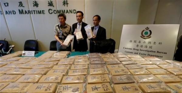 Funcionarios aduaneros  presentan los paquetes de cocaína en las instalaciones del Departamento de Aduanas de Hong Kong el viernes 6 de julio del 2012. Las autoridades realizaron la mayor redada antidrogas que se haya registrado en la ciudad, con la incautación de 649 kilogramos (1.430 libras) de cocaína en un contenedor procedente de Ecuador,  por un valor de 98 millones de dólares en su venta callejera. (Foto AP/Kin Cheung)