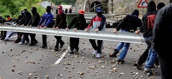 Un grupo de mineros usa una barra ferroviaria para bloquear una carretera como protesta en Cinera, cerca de León, España, el lunes 11 de junio del 2012. Las huelgas, bloqueos de caminos y sentadas en las minas continuaban mientras 8.000 mineros de 40 minas de carbón del norte de España protestaban por los recortes de subsidios anunciados por el gobierno debido a la crisis económica. (Foto AP/Juan Manuel Serrano)