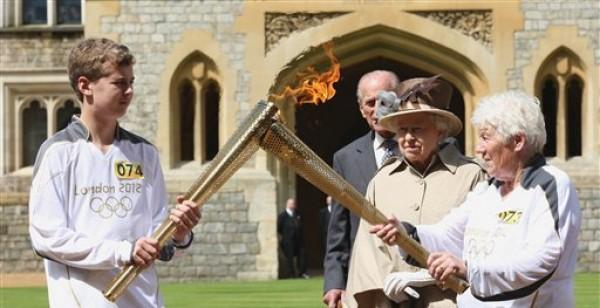 En esta imagen suministrada por el comité organizador de los Juegos Olímpicos, la reina Isabel II, segunda desde la derecha, y el Duque de Edimburgo observan a los portadores de la antorcha olímpica, Gina Macgregor, derecha, y Phillip Wells, a las afueras del castillo Windsor el martes, 10 de julio de 2012, en Inglaterra.    (AP Photo/Chris Radburn/LOCOG)