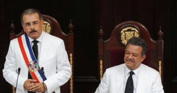 Danilo Medina, a la izquierda, asume la presidencia de República Dominicana con el reto de reducir la pobreza y convertir el constante crecimiento económico del país en desarrollo social. A la derecha el mandatario saliente Leonel Fernández. Santo Domingo, jueves 16 de agosto de 2012. (AP Photo/Manuel Diaz)