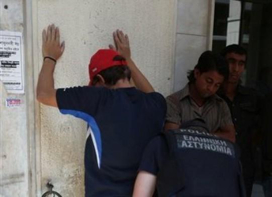 Un policía catea a un inmigrante en el centro de Atenas, el domingo 5 de agosto de 2012.  (Foto AP/Thanassis Stavrakis)