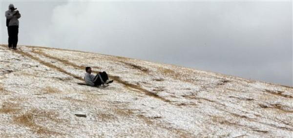 Un joven se desliza por una colina tras una inusual nevada en Johannesburgo, el martes 7 de agosto del 2012. (Foto AP/Themba Hadebe)