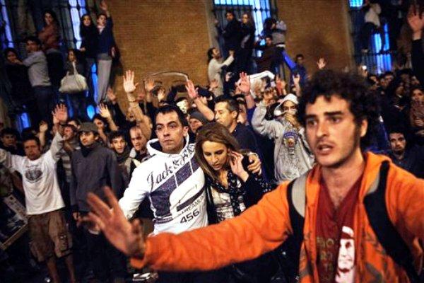 Manifestantes reaccionan tras los enfrentamientos de la policía con integrantes de la marcha que realizaban realizar frente al Parlamento en protesta por las medidas de seguridad impuestas por el gobierno en Madrid, el 25 de septiembre del 2012. La policía española afirmó el miércoles que 38 personas fueron arrestadas y otras 64 estaban heridas.  (Foto AP/Daniel Ochoa De Olza)