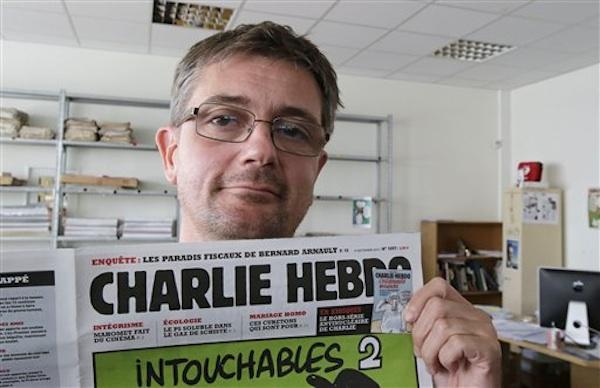 El director editorial del semanario satíŒrico Charlie Hebdo, Charb, muestra la primera página de la publicació›n mientras posa para fotografíŒas en ParíŒs, el miéˆrcoles 19 de septiembre de 2012.  (AP foto/Michel Euler)