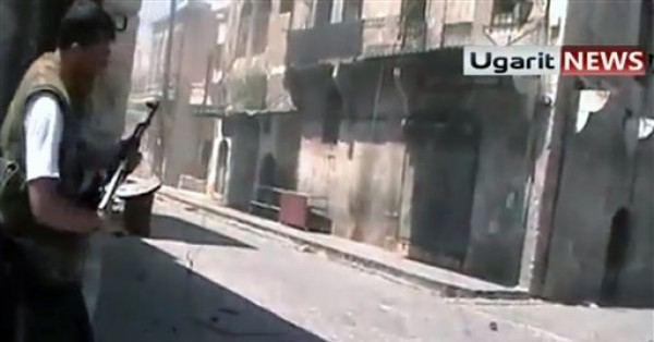 Una imagen tomada de un video aficionado divulgado por Ugarit News, tomado el domingo 26 de agosto del 2012, muestra a un rebelde del grupo Brigada Unificación mientras se prepara a disparar a un grupo de soldados en una calle de Alepo, en el norte de Siria. Helicópteros militares arrojaron el martes cientos de volantes sobre Damasco y los suburbios capitalinos, instando a los rebeldes a que entreguen sus armas o a enfrentarse a una inevitable muerte. (Foto AP/Ugarit News via AP video)