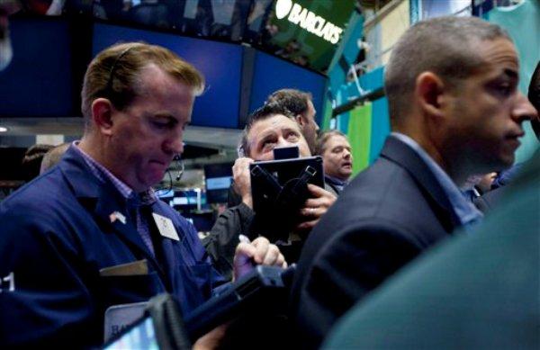 Corredores bursátiles en pleno trabajo en esta foto de archivo del viernes 10 de agosto del 2012 en la Bolsa de Valores de Nueva York.  Las bolsas de Asia caían el miércoles 22 de agosto del 2012  tras el anuncio de Japón sobre el déficit de su balanza comercial el mes pasado. (Foto AP/Jin Lee)
