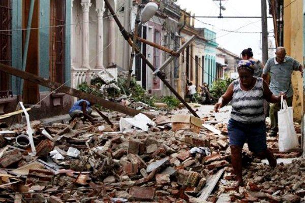Algunos residentes caminan a través de los escombros de viviendas dañadas por el huracán Sandy en Santiago de Cuba, Cuba, el viernes 26 de octubre de 2012. (Foto AP/Franklin Reyes)