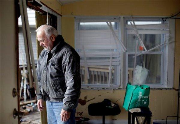 Chuck Clauser observa desde un agujero en la pared de su casa que resultó dañada por el huracán Sandy, en Cedar Bonnet Island, Nueva Jersey, el sábado 3 de noviembre de 2012. (Foto AP/Patrick Semansky)