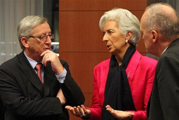 Christine Lagarde, al centro, que dirige el Fondo Monetario Internacional, conversa con el primer ministro de Luxemburgo y presidente del Eurogrupo Jean-Claude Juncker, a la izquierda, y otro funcionartio no identificado, durante la reunión de ministros de finanzas de la Eurozona en Bruselas, el lunes 12 de noviembre de 2012. (Foto AP/Yves Logghe)