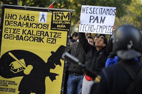 Un hombre que se identificó como Edwin, de 32 años y originario de Ecuador, y que fue desalojado de su casa por deudas, sostiene una pancarta durante una manifestación contra los deshaucios durante una huelga general organizada en protesta contra las medidas de austeridad, en Pamplona, España, el miércoles 14 de noviembre de 2012. (Foto AP/Alvaro Barrientos)