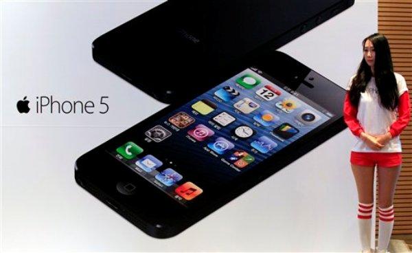 La foto del viernes 7 de diciembre de 2012 muestra a una mujer junto a un cartel publicitario del iPhone 5, en una tienda de teléfonos móviles en Seúl, Corea del Sur. En Estados Unidos, un juez advirtió que emitirá fallos para resolver de una vez la enredada batalla legal entre Apple Inc. y Samsung Electronics (AP Foto/Lee Jin-man)