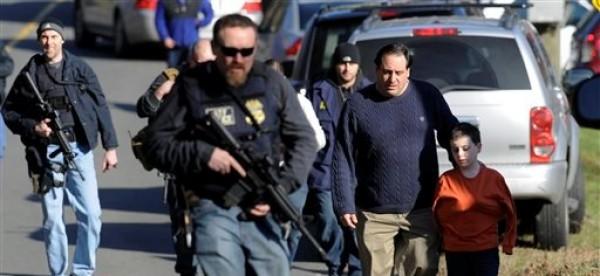 Varios padres se retiran con sus hijos entre agen tes policiales tras de que un individuo matara a tiros a 26 personas, incluidos 26 menores, en una escuela primaria en Newtown, Connecticutd, el viernes 14 de diciembre de 2012. (Foto AP/Jessica Hill)