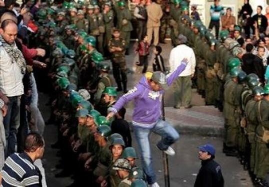 Una manifestante salta mientras soldados egipcios montan guardia frente al palacio presidencial de El Cairo el domingo 9 de diciembre de 2012. (Foto AP/Hassan Ammar)