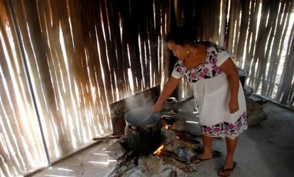 Donaciana Cupul cocina en su casita con estacas de madera en la comunidad maya de Hidalgo, en la península de Yucatán, en México, el 14 de diciembre. Como tantos otros mayas, a Cupul no le preocupa el fin de un ciclo de más de 5.000 años del calendario maya y sigue su vida como si nada. (AP Photo/Israel Leal)