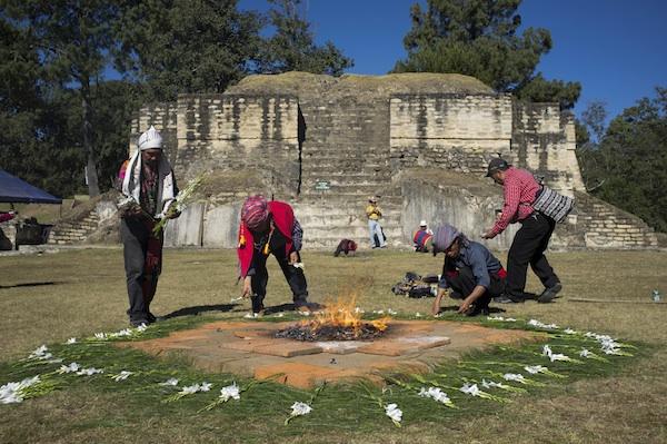Sacerdotes mayas colocan flores para una ceremonia en la zona arqueológica de Iximche, en Tecpan, Guatemala, el jueves 20 de diciembre de 2012. Aunque el calendario maya ha derivado en que muchas personas crean que el mundo se acabará el viernes 21, pocos descendientes de los mayas comparten esa idea (AP Foto/Moisés Castillo)