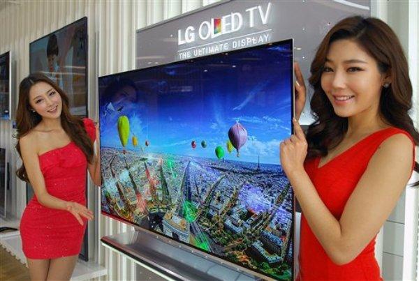 En esta foto distribuida por LG Electronics el miércoles 2 de enero de 2013, un par de modelos posa junto a un televisor OLED en Seúl (AP Foto/LG Electronics )