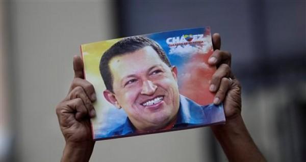 Un partidario del presidente venezolano Hugo Chávez sostiene un cartel con su imagen afuera de la Asamblea Nacional, en Caracas, Venezuela, el sábado 5 de enero de 2013. (Foto AP/Ariana Cubillos)