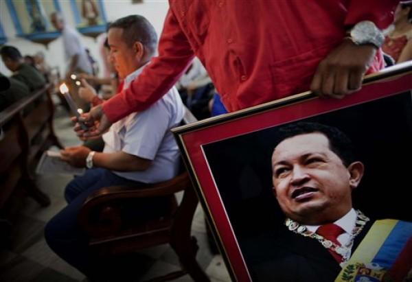 Un empleado de la embajada de Venezuela sostiene una imagen del presidente Hugo Chávez en una misa católica dedicada al mandatario venezolano, en la Iglesia de Nuestra Señora de Regla, en Regla, frente a La Habana, Cuba, el martes 8 de enero de 2013. Chávez no ha aparecido ni hablado en público desde su operación del 11 de diciembre en Cuba, alimentando las conjeturas de que difícilmente podrá asistir a su investidura el 10 de enero. (Foto AP/Ramón Espinosa)