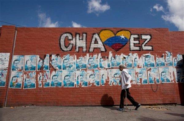 Una mujer pasa frente a un muro con carteles de la campaña de reelección del presidente venezolano Hugo Chávez en Caracas, Venezuela, el miércoles 9 de enero de 2013. El gobierno de Obama espera que el posible fin del gobierno de 14 años de Chávez ayude a Estados Unidos y Venezuela a restablecer una pragmática relación. (Foto AP/Ariana Cubillos)