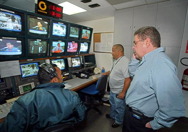 "Alberto Federico Ravel (R) chairman of private ""Globovision"" broadcast television, opposite to President Hugo Chavez, talks to technicians inside the editing room, 03 October 2003 in Caracas. Venezuela's Telecommunications National Commision (CONATEL) representatives confiscated live transmission equipments based on ""traces that Globovision has been using the radio spectrum without Conatel's authorization"", Commission's chairman Alvis Lezam said.   AFP PHOTO/Juan BARRETO   (Photo credit should read JUAN BARRETO/AFP/Getty Images)"